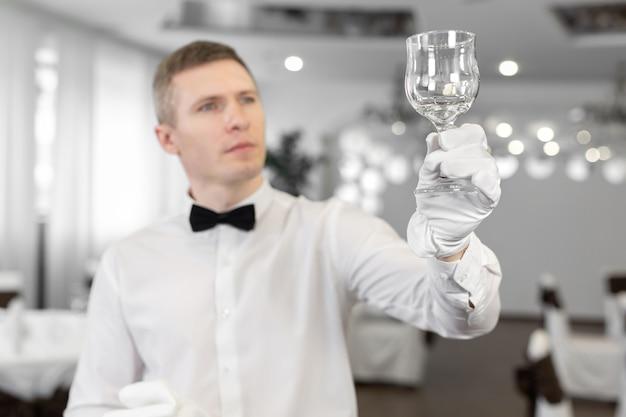 白い手袋をはめた男性ウェイターがワイングラスをこすります