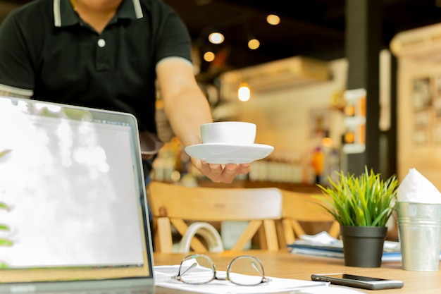 Male waiter serving coffee with laptop and glasses on working table in cafe.