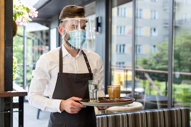 Cameriere maschio che indossa la maschera