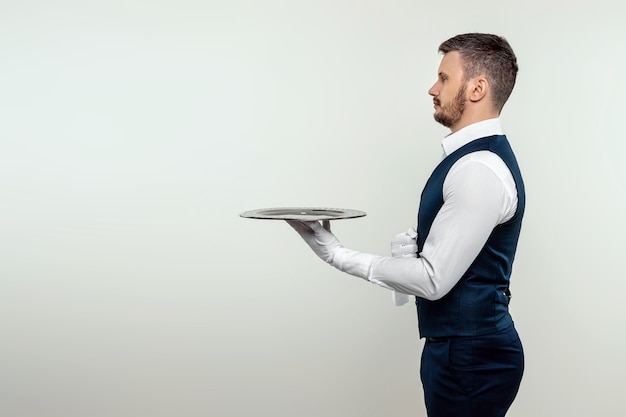 A male waiter in a white shirt stands sideways with a silver tray. the concept of service personnel serving customers in a restaurant.