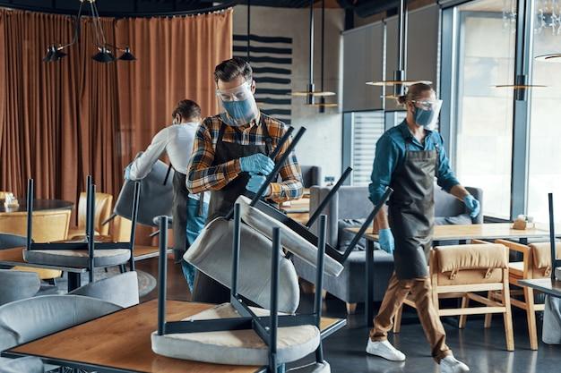 Официанты-мужчины в защитной спецодежде расставляют мебель в ресторане