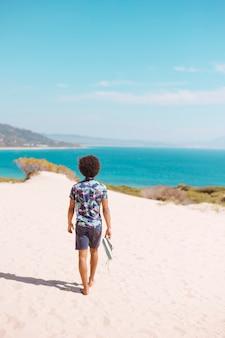 해변에서 맨발로 걷는 남자