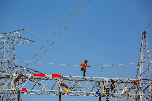 Male walking on the beam steel installation of high-voltage  transmission electricity poles the on line work at height risk should wear safety full body harness