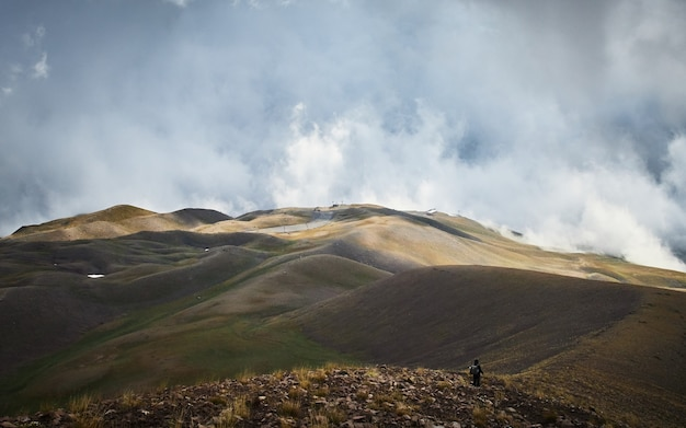 Male walking on a mountain with a cloudy sky