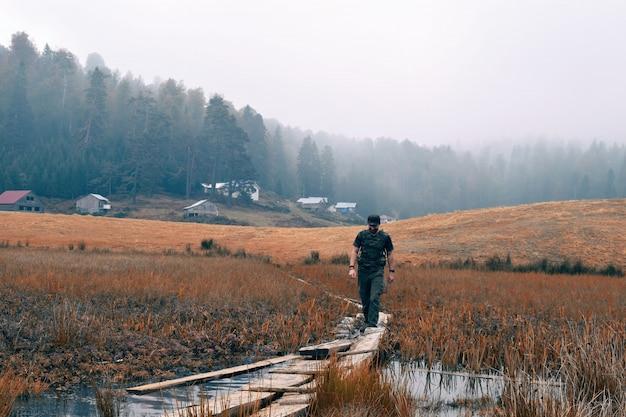木と乾いた草原の真ん中にある狭い木製の小道を歩く男性
