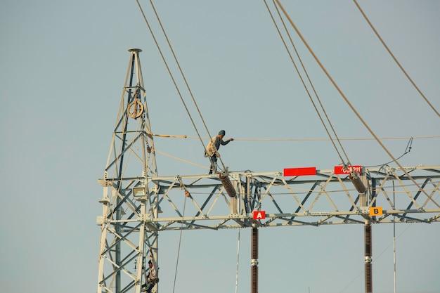 梁の上を歩く男性高電圧電柱の設置は、高さの危険がある作業をポールします