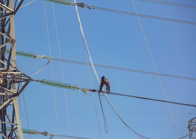 ライン電気を歩く男性高電圧電柱の設置は、高所での作業を危険にさらし、安全な全身ハーネスを着用します。