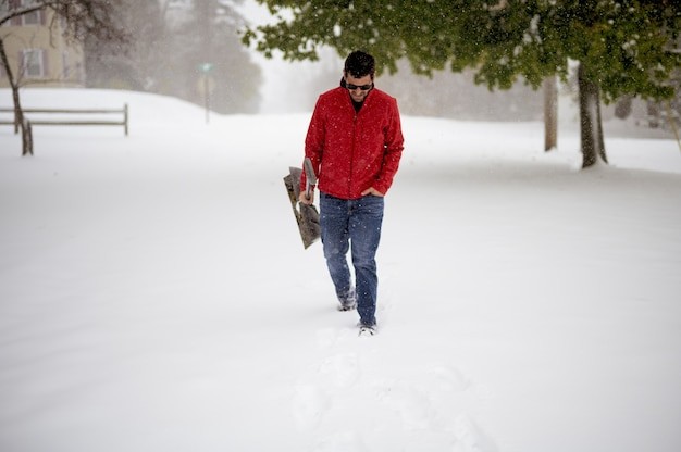 Male walking on a snowy field while holding the snow shovel