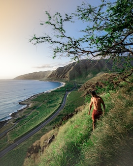 Male walking on a steep green hill with the beautiful sea and hills in the
