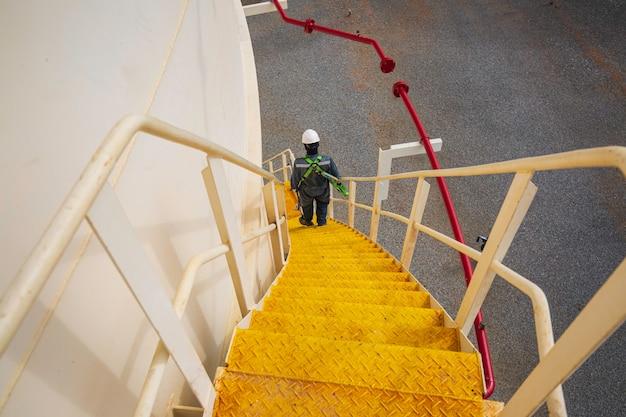 계단을 내려가는 남성은 높은 곳에서 시각적 기록 저장 탱크 안전 장치 작업을 합니다.
