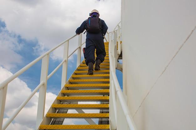 측면 푸른 하늘에 계단 검사 시각 기록 저장 탱크 계단을 걷는 남성.