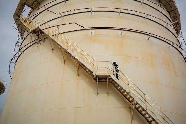 계단을 올라가는 남성은 시각적 기록 저장 탱크를 검사합니다.