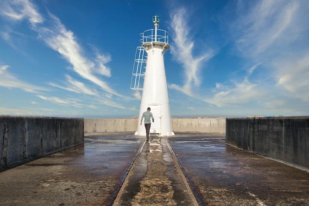 南アフリカ、イーストロンドンの灯台に向かって歩く男性。
