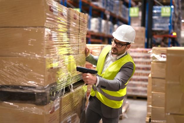 Работник склада-мужчина, использующий сканер штрих-кода для анализа вновь прибывших товаров для дальнейшего помещения в склад