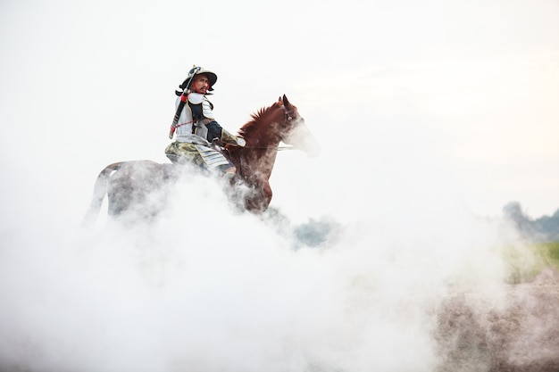 Male warrior in armor riding horse in white fog