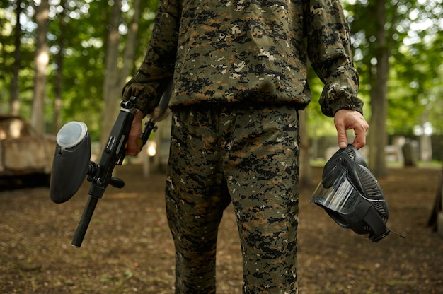 Male warrior in camouflage holds protection mask and paintball gun. extreme sport with pneumatic weapon and paint bullets or markers, military team game outdoors, combat tactics