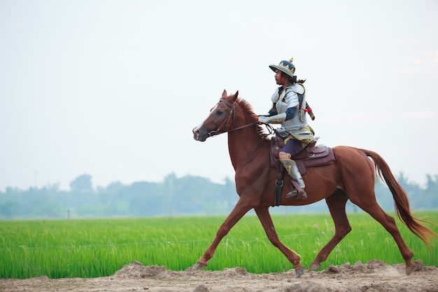 Male warrior in traditional armor riding horse