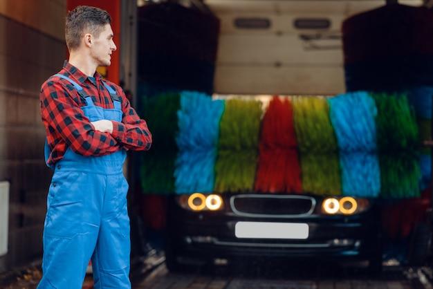 Мойщик в униформе на автоматической автомойке