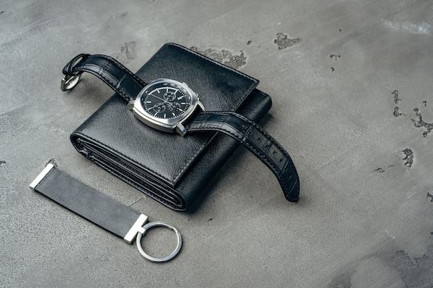 ダークグレーの表面に男性の時計と革の財布をクローズアップ