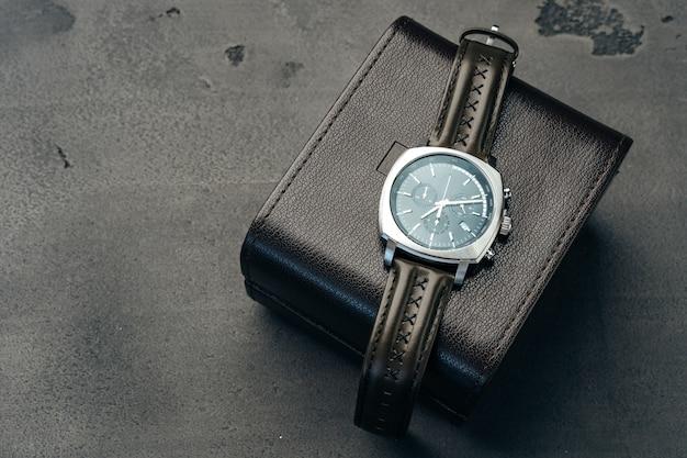 男性の時計とダークグレーの表面の革の財布がクローズアップ