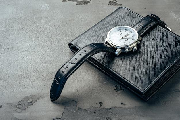 ダークグレーの表面に男性の時計と革の財布