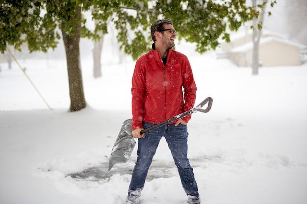 Мужчина в красной зимней куртке и держит снежную лопату, улыбаясь