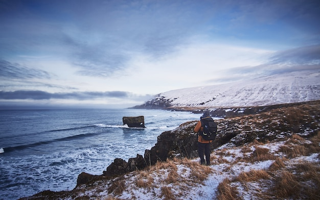 Male wearing a backpack and a jacket standing on the snowy hill while taking a picture of the sea