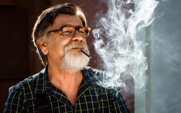 眼鏡をかけ、タバコを吸う男性