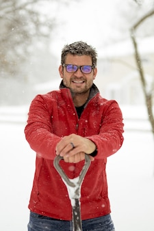 Male wearing a red winter jacket with his hands on a snow shovel