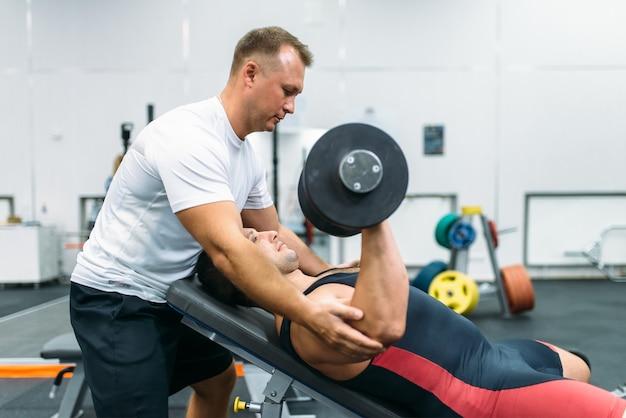 男性の重量挙げ選手はベンチに横たわり、インストラクターの管理下でダンベルを使って運動し、ジムのインテリアを作ります。