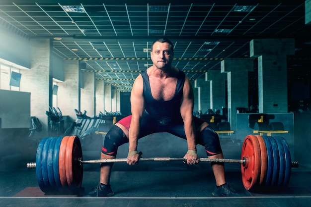 Male weightlifter prepares to pull heavy barbell, deadlift, gym interior. weightlifting workout in sport or fitness club, bodybuilding