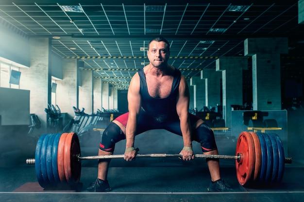 Тяжелоатлет мужского пола готовится тянуть тяжелую штангу, становую тягу, интерьер тренажерного зала. тяжелая атлетика в спортивном или фитнес-клубе, бодибилдинг