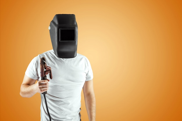 Male welder in a helmet on an orange background.