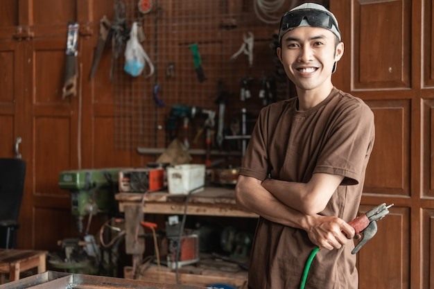 Male welder smiles with crossed hands while holding electric welder in welding workshop background