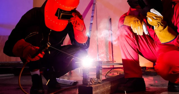 Male welders working together at site.