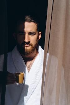 Male in white bathrobe with coffee mug in hand.