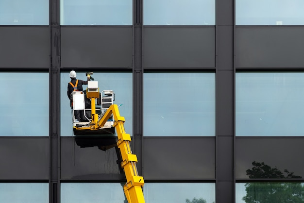 남성용 창문 청소기는 엘리베이터 플랫폼에 있는 현대적인 건물의 유리창을 청소합니다. 공중에 떠있는 작업자 연마 유리