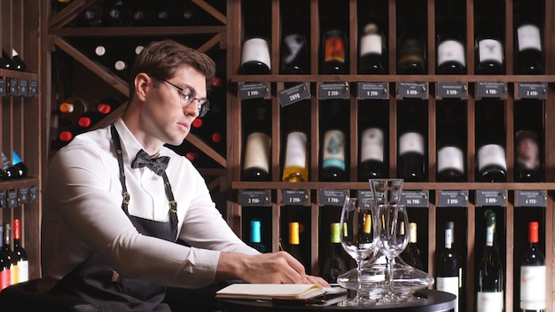Male wine steward makes an inventory of wine in the store, writes some notes in a notebook next to racks of wine bottles