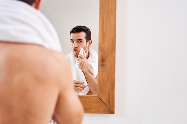 男性は朝風呂で鏡のそばに立っている間彼のタオルを拭く