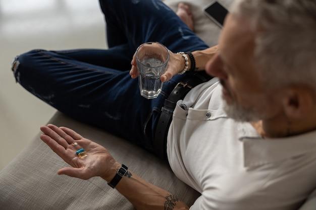 彼の薬を服用しているコップ一杯の水を持つ男性