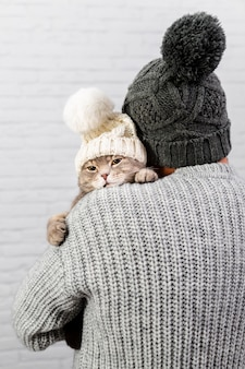 Male with back holding cat with fur cap