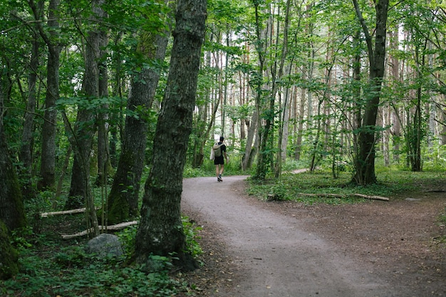 Male with a backpack walking on a pathway in the middle of the forest