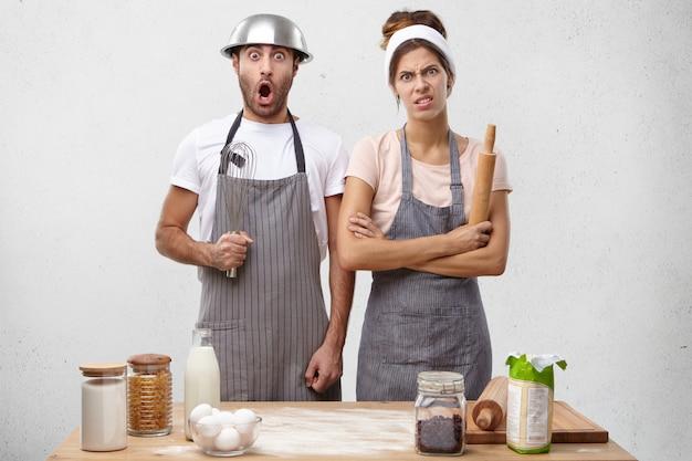 Мужчина с миской на голове и венчиком в руках с возбужденным потрясенным взглядом