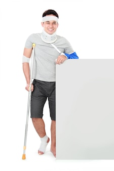 Male with broken arm and crutch holding blank banner