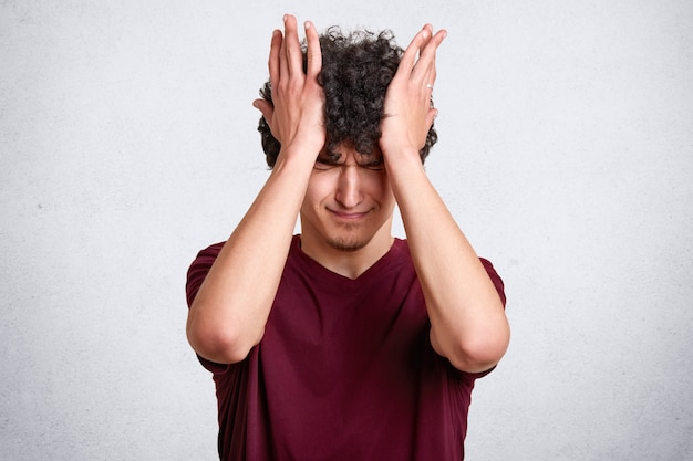 Male with curly hair, wears casual maroon t shirt, has unhappy expresions, touches his head with hands isolated on white. copy space for your advertisment or promotional text.