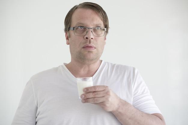 Uomo con gli occhiali in possesso di un bicchiere di latte sotto le luci isolate su bianco
