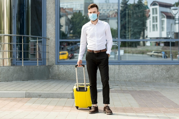 Male with luggage wearing mask