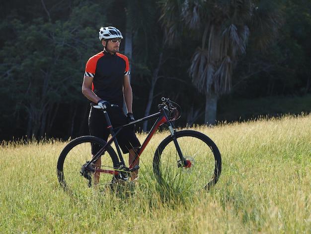 マウンテンバイクを持つ男性。マウンテンバイカーは休憩しながら景色を楽しんでいます。