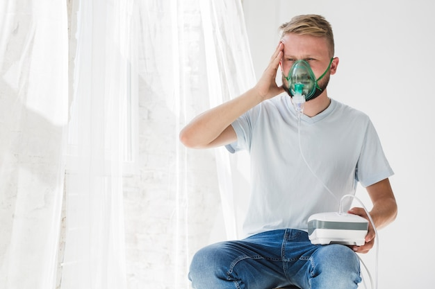 Male with nebulizer holding head
