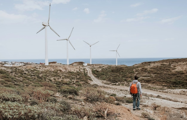 A male with a red backpack standing and looking at the windmills